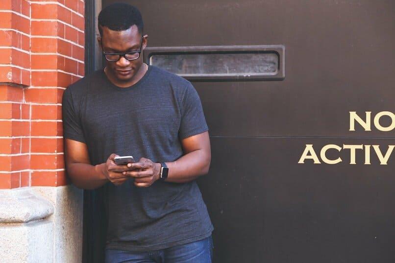 Mann mit  Helfer  ein Handy neben  eine Mauer