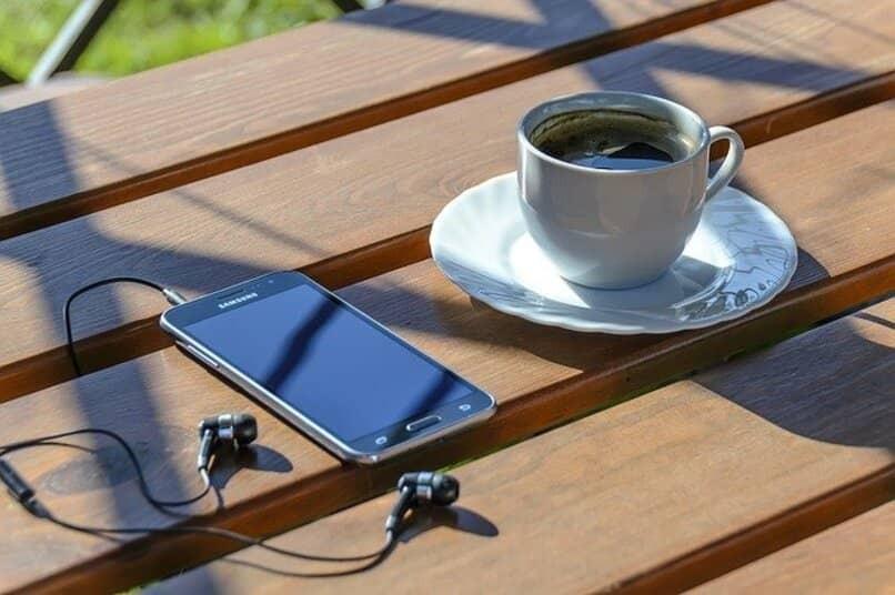 Samsung Galaxy S4 auf einer Bank neben einer Tasse Kaffee
