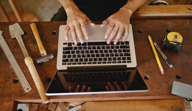 Hände auf einem PC auf einem Tisch mit Werkzeugen