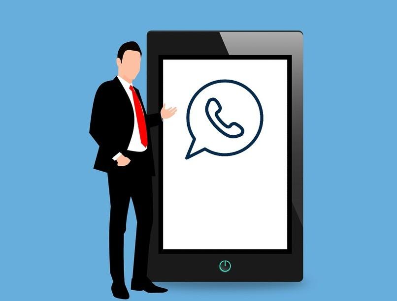 Mann, der neben einem iPad steht, das WhatsApp-Logo hat