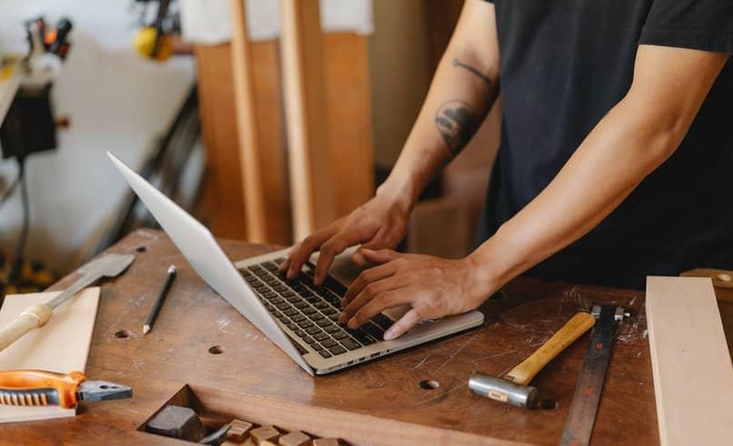 Mann, der auf einem Computer auf einem Tisch tippt