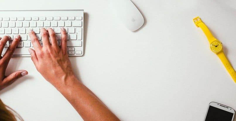 Person, die auf weißer Tastatur tippt